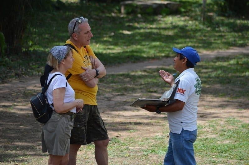 A tour guide with two tourists at the Acropolis pyramid at Ek Balam ruins, Mexico