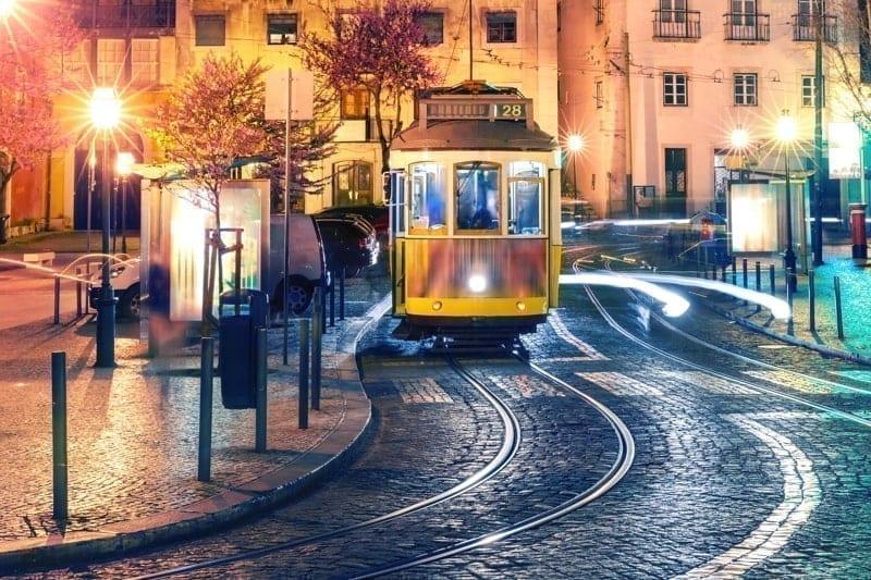 Yellow 28 tram in Alfama at night, Lisbon, Portugal.