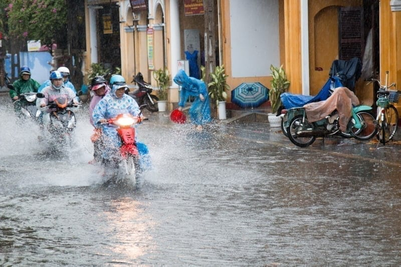 Hoi An, Vietnam. Heavy rain and storms in the wet season soak people and scooter riders