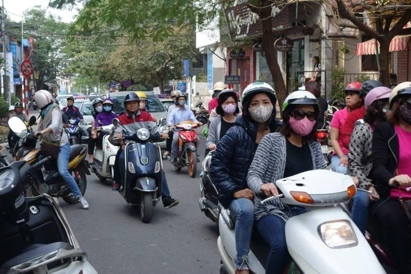 Scooters with riders, some wearing face masks, on a busy street in Hanoi, Vietnam