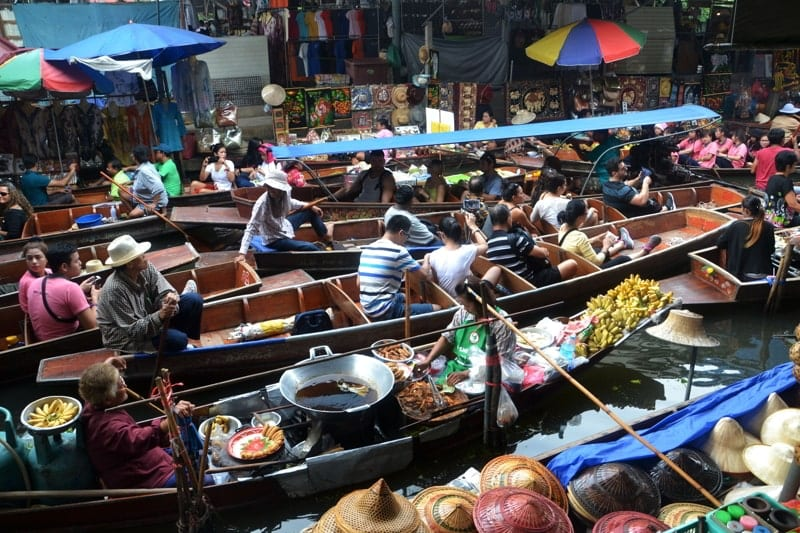 People on boats on a floating market in Thailand