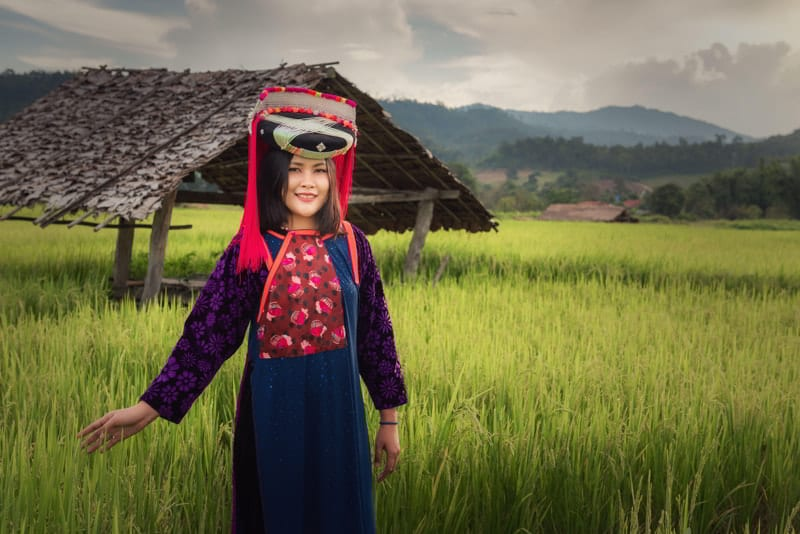 Portrait of Lisu woman in traditional dress and jewelry costume in rice fields in Thailand