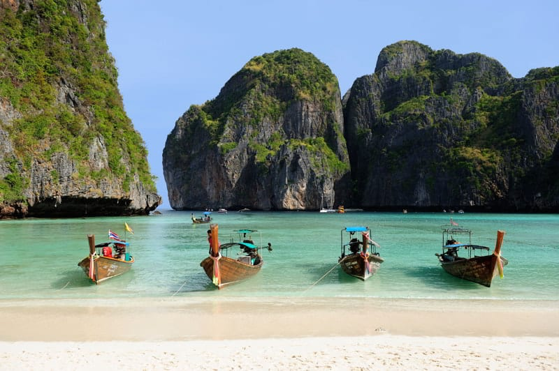 Four traditional wooden boats on turquoise waters of a beautiful white sand beach on Phi Phi Island, Thailand, Asia