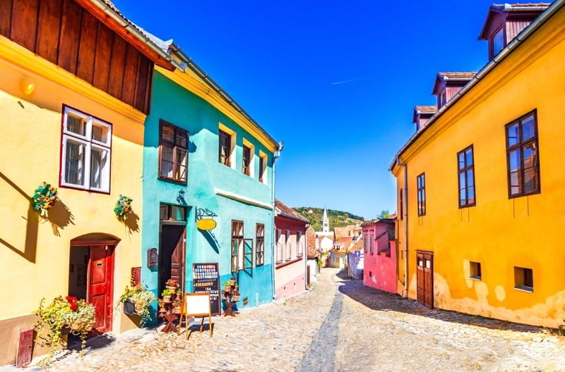 Famous stone paved old streets with colorful houses in Sighisoara, Romania.