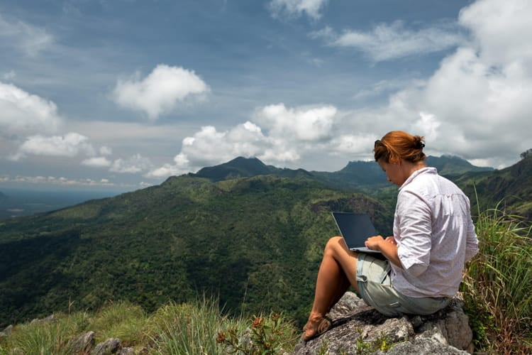 Girl working on her computer on the top of the mountain.
