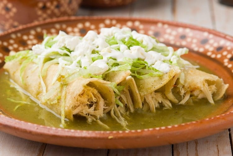 Mexican green chicken enchiladas served on a traditional clay plate