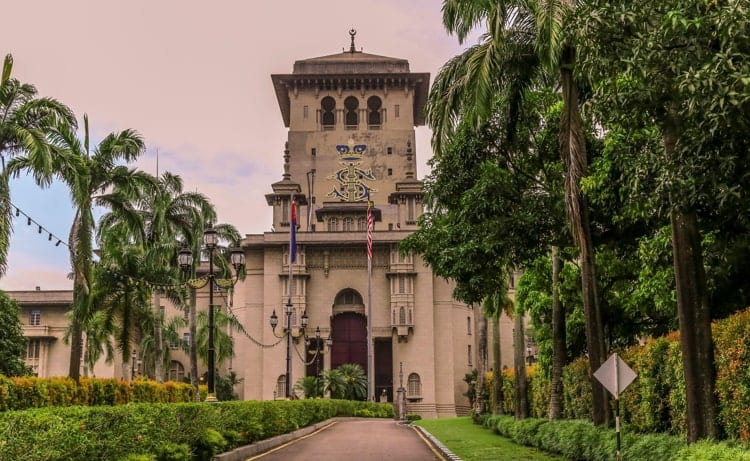 Surrounded by trees and shrubs the walkway leads to the Sultan Ibrahim Building in Johor Bahru Malaysia