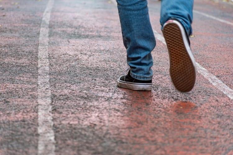 Man wearing jeans and sneaker shoes walking in empty street
