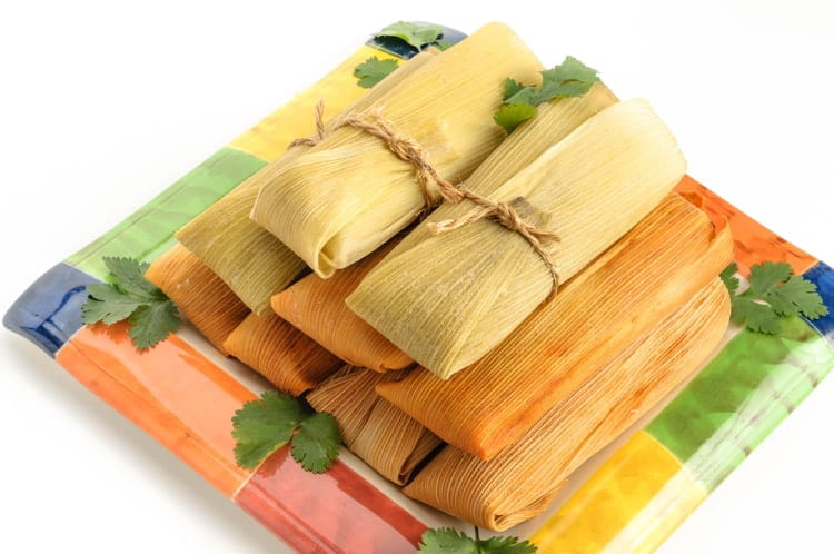 Tamales, Mexican dish made with corn dough, chicken and chili, wrapped with a corn leaf