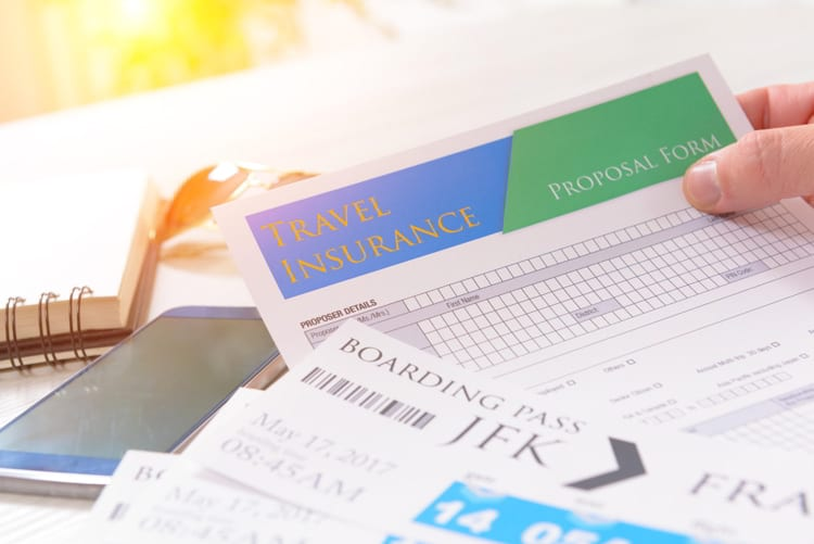 Airline boarding pass tickets in hand with travel insurance, sunglasses, pen and notebook