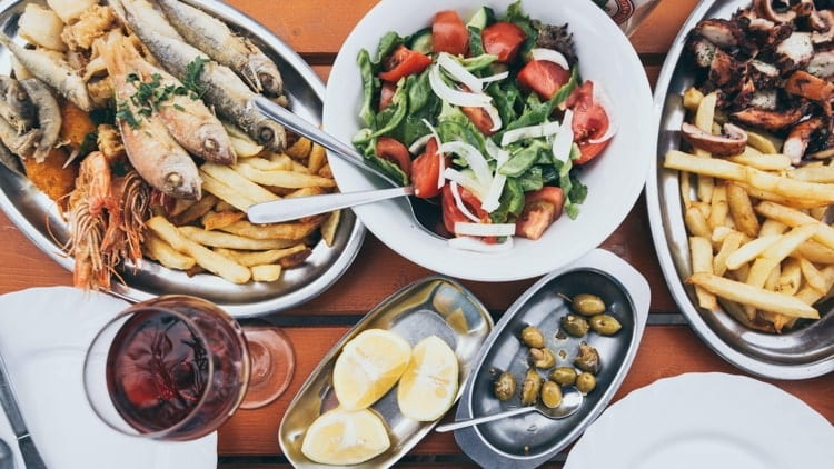 Flat lay of Cyprus fish and seafood meze with olives, lemon and Greek salad.