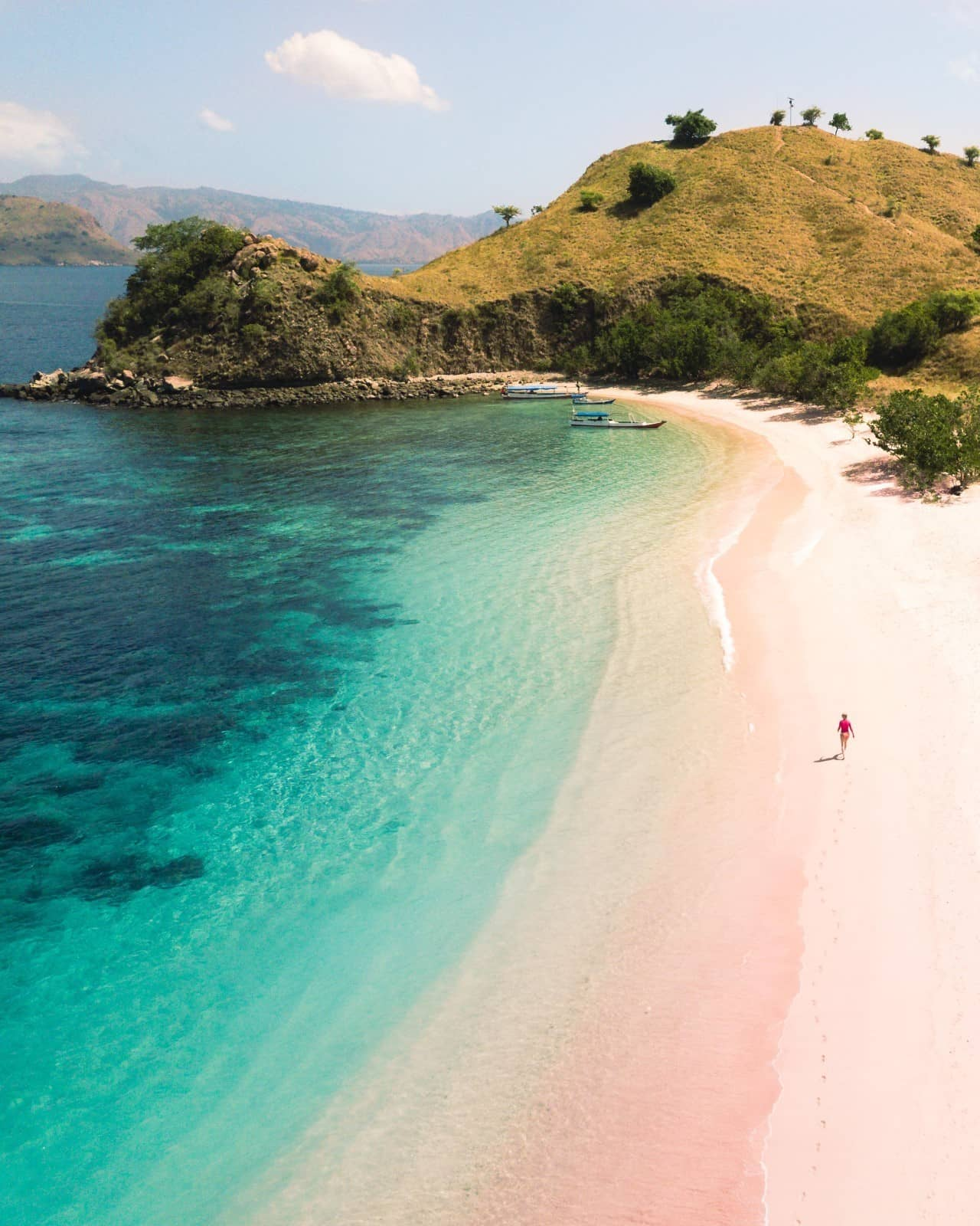 Woman walking on the exotic Pink Beach in Indonesia