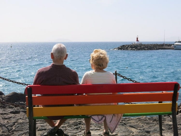Rear view of an elderly couple sitting on a multi-coloured bench, enjoying some winter sunshine abroad & looking out to sea