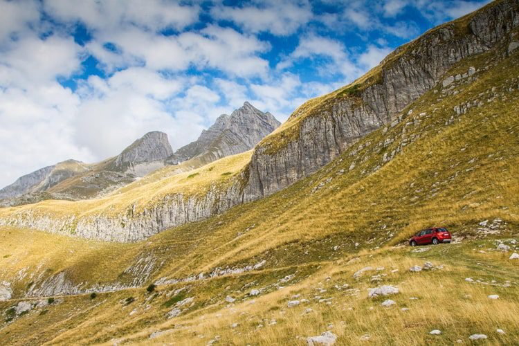 Durmitor National Park in Montenegro with green gras and a red car