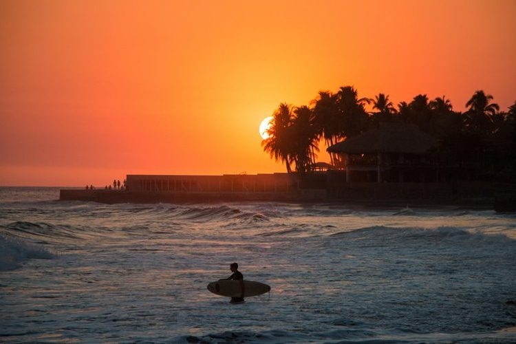 Surfer in the water during a sunset at Playa el Tunco, El Salvador