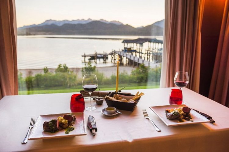 Table set up for dinner at a fine dining restaurant with a glass of red wine, delicious Argentinian steak and beautiful views of lakes and mountains, Patagonia, Argentina