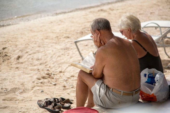 Retired couple sitting on a beach reading a book