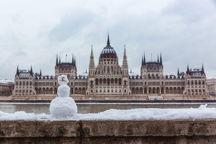Hungarian parliament building at winter with snow. Snowman on the river bank