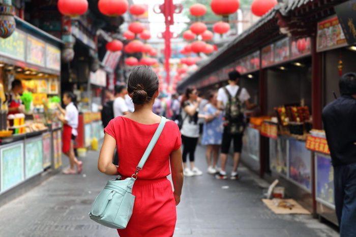 Woman walking in Wangfujing food street in China