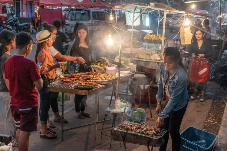 A market in Laos with people selling food