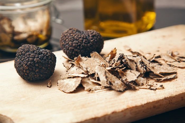 Two truffles and truffle shavings on a cutting board