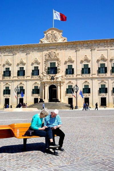 View of the Auberge de Castille in Castille Square with a couple sitting on a bench in the foreground, Valletta, Malta